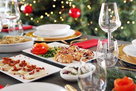 Piatti festosi su una tavola elegante. Piatti natalizi, tavola festiva. Composizione orizzontale.