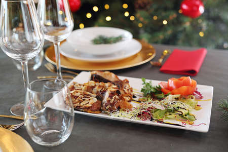 Fish baked in almonds, an elegant dish on a festive table. Traditional Christmas dishes, festive table setting. Horizontal composition.