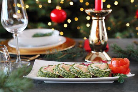 Spinach roulade with salmon and cottage cheese. Christmas dishes, festive table setting. Horizontal composition. Reklamní fotografie
