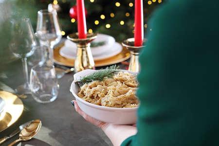 Christmas dinner, woman serves traditional Christmas dishes at the table. Traditional Christmas dishes, festive table setting. Horizontal composition.