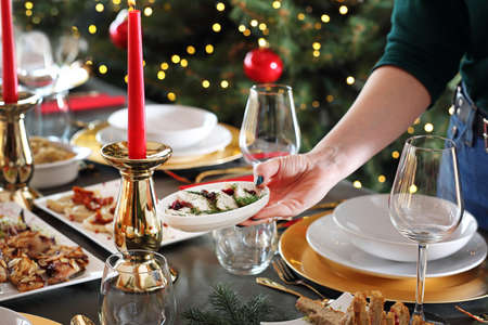 Herrings in oil, a gourmet snack on the holiday table. Christmas dishes, festive table setting. Horizontal composition. Reklamní fotografie