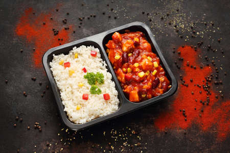 Chicken in a Mexican sauce with rice, a takeaway container. Reklamní fotografie