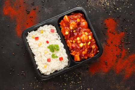Catering. Chicken in Mexican sauce with rice. Ready dish in a black container. Composed take-out meal, diet catering. The container on a dark background.