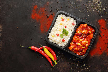 Box diet. Chicken in Mexican sauce with rice. Ready dish in a black container. Composed take-out meal, diet catering. The container on a dark background.