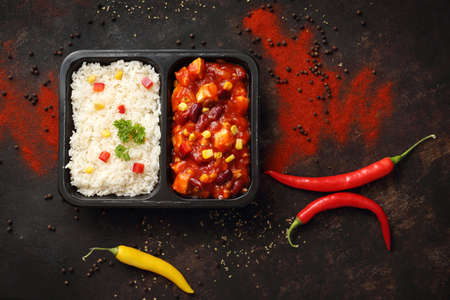 Dietetic catering. Chicken in Mexican sauce with rice. Ready dish in a black container. Composed take-out meal, diet catering. The container on a dark background.