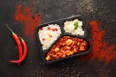 Box diet. Chicken in Mexican sauce with rice and salad. Ready dish in a black container. Composed take-out meal, diet catering. The container on a dark background.