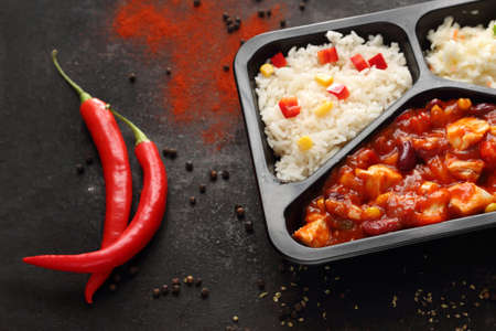 Chicken in Mexican sauce with rice and salad, dish in take-out container. Ready dish in a black container. Composed take-out meal, diet catering. The container on a dark background.