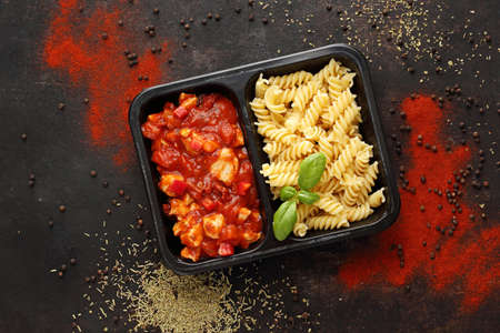 Ready dish in a black container. Composed take-out meal, diet catering. The container on a dark background. Reklamní fotografie