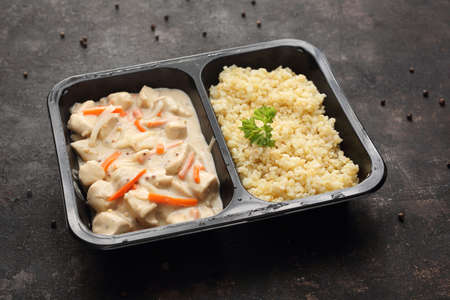 Chicken in mustard sauce with bulgur, dish in a take-out container. Ready dish in a black container. Composed take-out meal, diet catering. The container on a dark background.