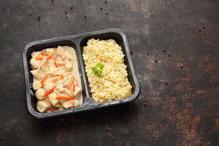 Dietetic catering, Chicken in mustard cream sauce with bulgur groats. Ready dish in a black container. Composed take-out meal, diet catering. The container on a dark background.