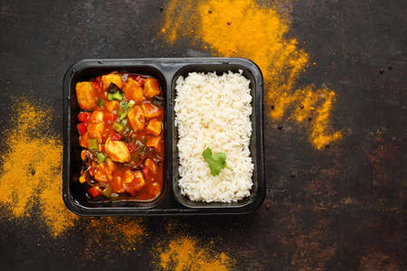Dietary catering, Chinese chicken with white rice. Ready dish in a black container. Composed take-out meal, diet catering. The container on a dark background.