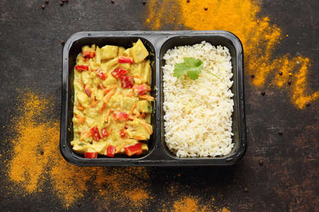Chicken in curry sauce with rice, a takeaway container. A meal in a box. Ready dish in a black container. Composed take-out meal, diet catering. The container on a dark background.