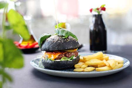 Black burger. A tasty burger in a black roll.