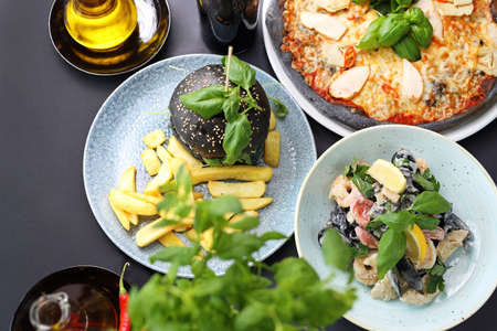 Black food. Burger, pizza, pasta, dishes with activated charcoal.