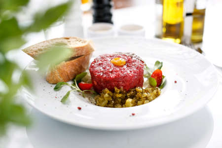 Beef tartare with egg and pickles. Appetizing appetizer. Suggestion to serve the dish. Culinary photography. Reklamní fotografie