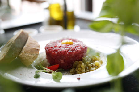 Chopped beef, steak tartare served with yolk and pickles. Appetizing appetizer. Suggestion to serve the dish. Culinary photography.