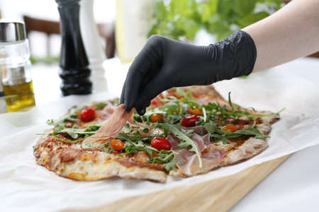 Italian pizza with ham. The cook is preparing a delicious pizza. Traditional Italian pizza with Parma ham, cherry tomatoes and arugula.