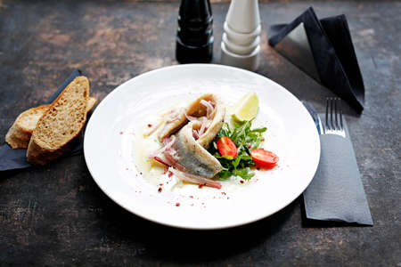 Herring in oil with onion and fresh vegetable salad. Appetizing appetizer. Suggestion to serve the dish. Culinary photography.