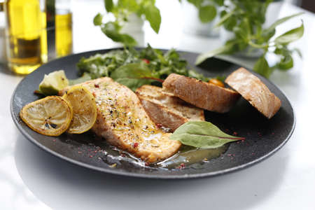 Salmon in lemon sauce. Appetizing dinner dish served with salad and bread. Food photography, food styling.