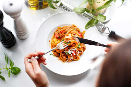 Spaghetti Bolognese. The woman is eating pasta. Spaghetti Bolognese. Appetizing dish served on a white plate. culinary photography.