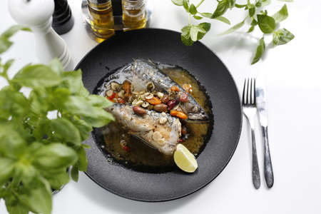 mackerel. Whole fish served with garlic, olives, and lemon. Appetizing dish served on a black plate .Culinary photography, food photography. Reklamní fotografie