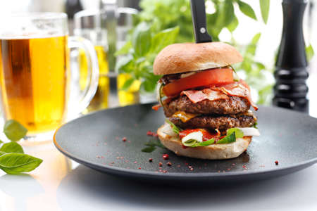 Hamburger with two beef cutlets, tomato, lettuce, and sauce. Burger on a plate. A large burger with beef, tomato, lettucAppetizing dish served on a black plate .Culinary photography, food photography.