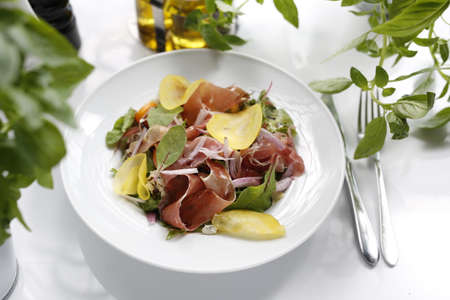 Salad with Parma ham, tomatoes, yellow beetroot, and vinaigrette sauce. Appetizing dish served on a white plate. culinary photography.