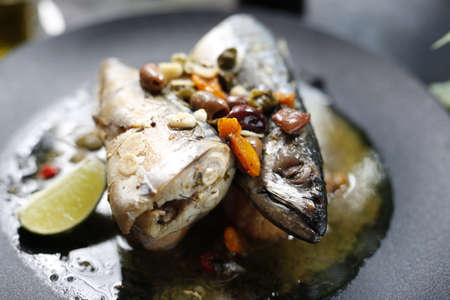 Roasted mackerel. Whole fish served with garlic, olives, and lemon. Appetizing dish served on a black plate .Culinary photography, food photography.