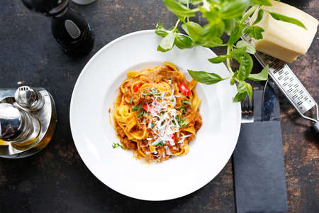 Tagliatelle with tomato sauce, traditional Italian cuisine. Appetizing dish served on a white plate. culinary photography.