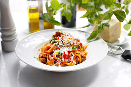 Tagliatelle with bolognese sauce, pasta with tomato sauce, and cheese. Traditional Italian cuisine. Appetizing dish served on a white plate. culinary photography.