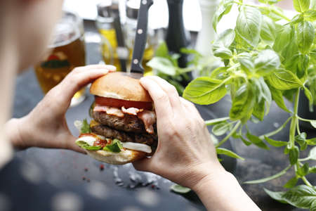 eating a hamburger. Appetizing dish served on a black plate .Culinary photography, food photography.