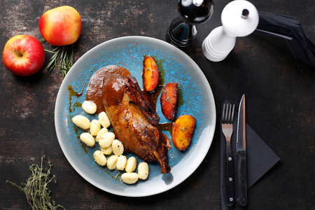 Roast duck with apples in a roast sauce with dumplings. Appetizing dish served on a plate. culinary photography, food styling.