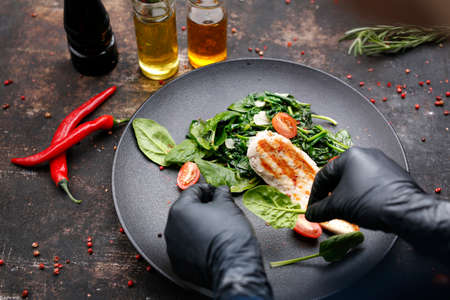 Grilled chicken fillet on spinach, dietary food. The cook cooks and serves an appetizing dish. The finished dish served on a plate. Serving proposal, culinary photography.