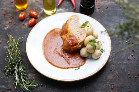 Stuffed cabbage with minced meat in tomato sauce served with potatoes. Ready dish served on a plate. Serving proposal, culinary photography.
