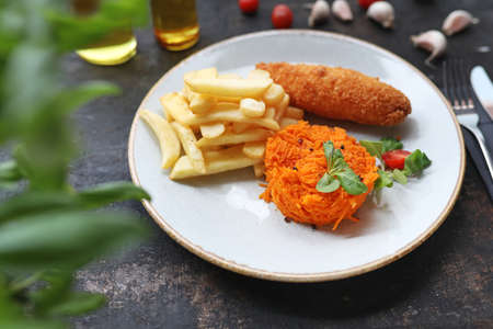 Cutlet de volaille with butter, fries and carrot salad. Dish on the plate, culinary photography.