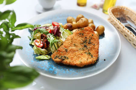 Pork chop with roasted potatoes and fresh vegetable salad. Dish on the plate, culinary photography. Stock fotó