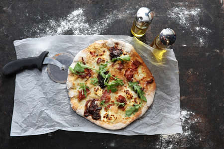Pizza with white sauce, bacon, caramelized onion, goat cheese, and arugula.