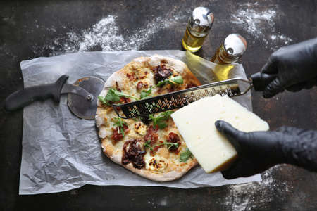 Pizza with white sauce, bacon, caramelized onion, goat cheese, and arugula. Pizza in a box. Pizza delivery. Culinary photography.
