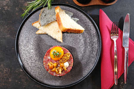 Beef tartare with yolk, pickled mushrooms and mustard. Traditional appetizer. Serving the dish. Stock fotó