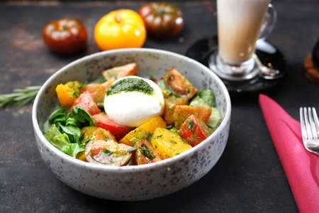 Mozzarella with green pesto served with colorful tomatoes on spinach leaves. A colorful, healthy breakfast. Food served on a plate, food styling, serving suggestions, culinary photography.