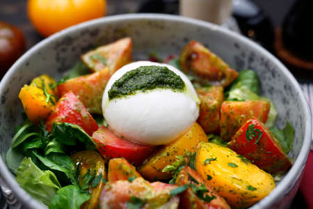 Mozzarella with green pesto served with colorful tomatoes on spinach leaves. A colorful, healthy breakfast. Food served on a plate, food styling, serving suggestions, culinary Stock fotó