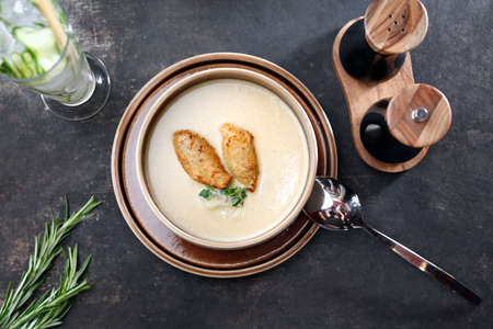 Cream soup. Creamy white vegetable soup. Food served on a plate, food styling, serving suggestions, culinary photography.