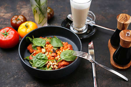 Tomatoes baked with spinach and peanuts. Food served on a plate, food styling, serving suggestions, culinary photography.