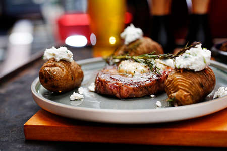 Beef steak with garlic butter, baked potatoes with cottage cheese. Food served on a plate, food styling, serving suggestions, culinary photography. Stock fotó