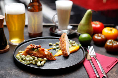 Roasted poultry fillet with broad beans and carrot puree .. Food served on a plate, food styling, serving suggestions, culinary photography.