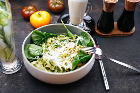 Pasta with green pesto with spinach, pine nuts and parmesan cheese. Food served on a plate, food styling, serving suggestions, culinary photography Stock fotó