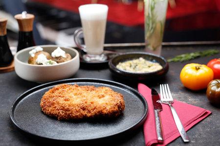 Pork chop fried in a crispy panko coating. Dish on a dark plate. Proposal menu. Stock fotó