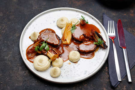 Elegant dinner. Meat in gravy with white vegetable puree. Food served on a plate, food styling, serving suggestions, culinary photography. Stock fotó