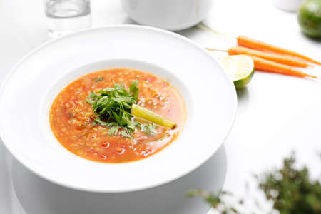 Red lentil soup with coriander and lime. A plate of aromatic and healthy soup. Lebanese cuisine. Lebanese red lentil soup with lime and coriander. A plate of aromatic and healthy soup.