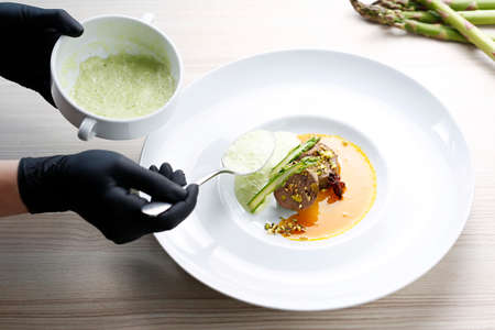 Goose terrine, roasted pistachios puree with asparagus served on an orange and anise sauce. A gourmet dish on a white plate. Food photography. The chef serves the dish. 版權商用圖片